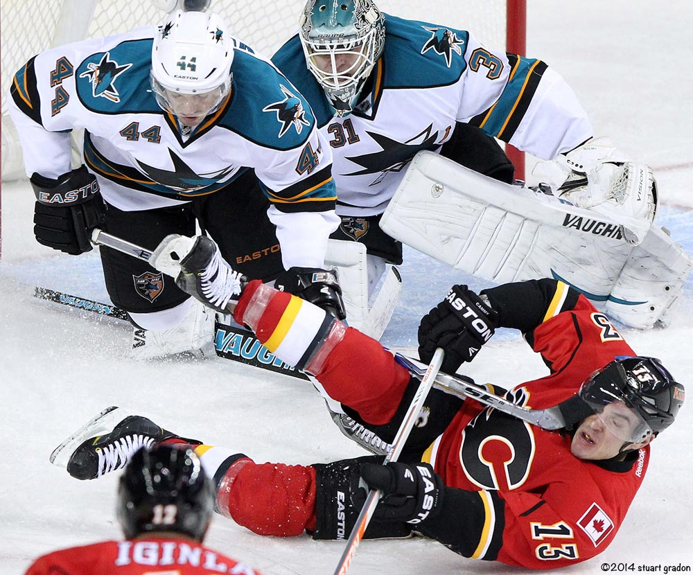 The Calgary Flames' Mike Cammalleri (bottom) has to contend with San Jose Sharks Mark Edouard Vlasic's stick under his visor in front of goalie Antti Niemi during the third period of their NHL game at the Scotiabank Saddledome in Calgary, Alberta January 20, 2013.